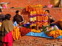 Unidentified women are making worship flowers in Bhaktapur Durbar Square area, Kathmandu, Nepal. Stock Image