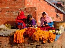 Unidentified women are making worship flowers in Bhaktapur Durbar Square area, Kathmandu, Nepal. Royalty Free Stock Photo