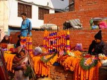 Unidentified women are making worship flowers in Bhaktapur Durbar Square area, Kathmandu, Nepal. Royalty Free Stock Images