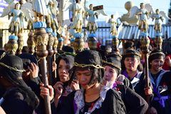 Unidentified Women penitents in garb and crown of bitter herbs carrying angel figurine scepter. San Pablo City, Laguna, Philippines - April 14, 2017 Stock Image