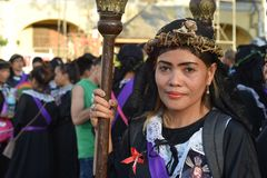 Unidentified Women penitents in garb and crown of bitter herbs carrying angel figurine scepter standing on the churchyard on Lente. San Pablo City, Laguna stock photos