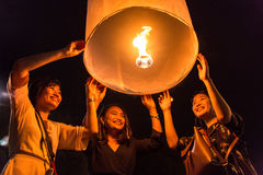 Unidentified women release Khom Loi, the sky lanterns during Yi Peng or Loi Krathong festival in Chiang Mai, Thailand. Stock Photo