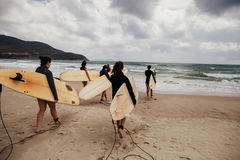 Unidentified women surfers with surfing boards coming to the sea Royalty Free Stock Photography