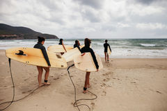 Unidentified women surfers with surfing boards coming to the sea Stock Images