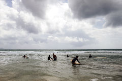 Unidentified women surfers with surfing boards coming to the sea Stock Photos
