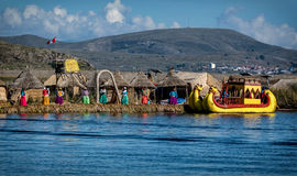 Unidentified women welcome tourist on the lake Titicaca in Puno, Royalty Free Stock Photo