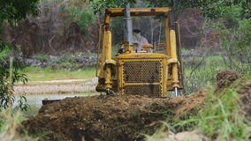 Unidentified worker control Bulldozer to excavator grader removing the ground stock video