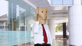 Unidentified worker makes phone call in office lobby. Unidentified businessman with paper bag on his head, making a phone call while standing in the office lobby stock video