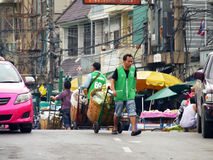 An unidentified worker pushes a cart full of vegetables through the vegetable market Stock Photos