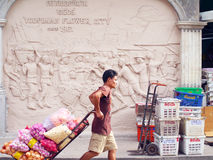 An unidentified worker pushes a cart full of vegetables through the vegetable market Stock Images