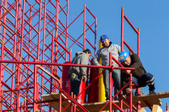 Unidentified workers setting up iron scaffolding at construction Stock Photo