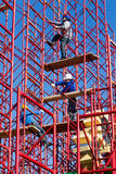 Unidentified workers setting up iron scaffolding at construction Stock Photos