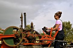 Unidentified young lady operates a restored steam engine Royalty Free Stock Photos