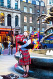 Unidentified young man with a bagpipe in the Scottish national dress at Piccadilly Circus Royalty Free Stock Photography