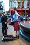 Unidentified young man with a bagpipe in the Scottish national dress at Piccadilly Circus Royalty Free Stock Photo