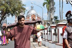 Unidentified young man playing role of thief carrying logs, street drama, community celebrates Good Friday representing the events. San Pablo City, Laguna stock photography