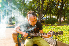 An unidentified young man plays guitar and smokes cigarette in M Royalty Free Stock Photography