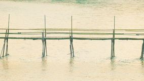 Unidentified young people pass long bamboo bridge above river Royalty Free Stock Photos