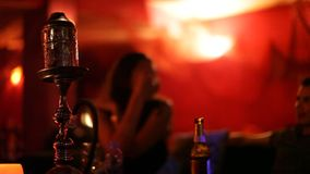 Unidentified young people smoking Shisha water pipe in a bar stock video