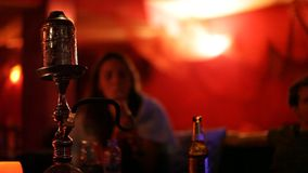 Unidentified young people smoking Shisha water pipe in a bar stock video footage