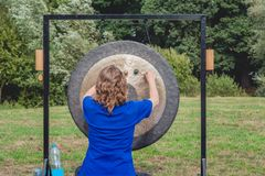 Woman gives a demonstration with a big gong. Unidentified young woman gives a demonstration with the rhythmical beating of a large gong in a Dutch park on a royalty free stock photography