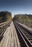 An unidetified lonely man on the old train bridge. Unidentified lonely man walks over the old train bridge over the Bobr river in Bobr Valley in Poland in autumn Stock Image