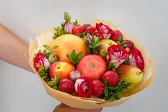 Uniek feestelijk boeket die uit appelen, peren, pruimen, grapefruits en bloeiende rozen in de handen van een meisje bestaan royalty-vrije stock afbeeldingen