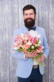 Unieke bloemstukken De lentegift Gebaarde mens hipster met bloemen Bloem voor 8 Maart De datum van de liefde internationaal stock afbeeldingen
