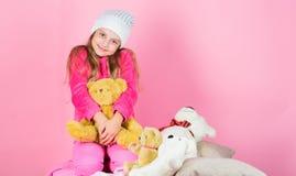 Unieke gehechtheid aan gevulde dieren Het spel van het jong geitjemeisje met zachte stuk speelgoed teddybeer roze achtergrond Kin stock foto