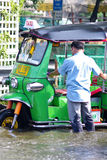 Unientified driver shove his Tuk tuk thru flood Stock Photos