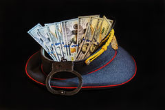 Uniform cap with American dollars and handcuffs Stock Photos