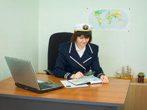 In uniform of captain examines geographical. Beauty in a uniform of the sea captain examines the geographical atlas royalty free stock image