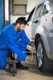 Uniform mechanic working on tyre Royalty Free Stock Photo