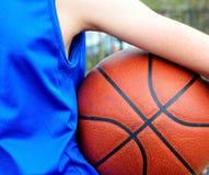 Uniforme d'uso del blu del giocatore di pallacanestro con la palla immagini stock libere da diritti