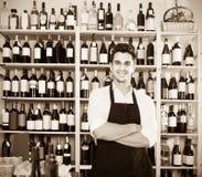 Uniforme d'uso del venditore dell'uomo che sta nel negozio con vino Fotografia Stock