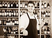 Uniforme d'uso del venditore dell'uomo che sta nel negozio con vino Fotografie Stock