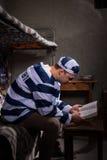 Uniforme de port de prison de prisonnier lisant un livre ou une bible tandis que photos stock