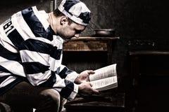 Uniforme de port de prison de prisonnier masculin lisant un livre ou une bible W photographie stock libre de droits