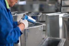 Uniforme del azul del calafateo asiático del trabajador que lleva Imágenes de archivo libres de regalías