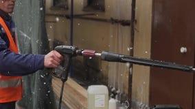 Uniforme del trabajador de sexo masculino joven y agua de los esprayes del casco que llevan para contener la fachada almacen de metraje de vídeo