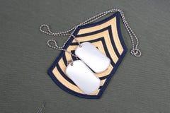 Uniforme dell'esercito americano con le medagliette per cani e la vegetazione lussureggiante in bianco di sergente Immagini Stock