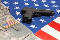Uniforme dell'esercito americano e della rivoltella sopra la bandiera enorme di U.S.A. Immagine Stock