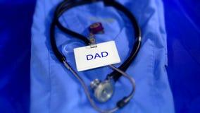 Uniforme dos cuidados médicos com o PAIZINHO da leitura do crachá de nome Fotografia de Stock Royalty Free
