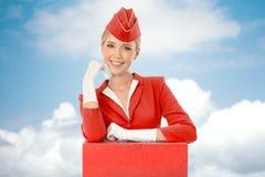 Uniforme encantador e mala de viagem de Dressed In Red da comissária de bordo Fotos de Stock Royalty Free