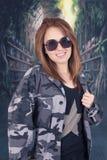 Uniforme militar y gafas de sol que llevan de la chica joven Imagenes de archivo