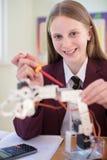 Uniforme scolaire de port d'élève femelle dans la leçon de la Science étudiant R photos libres de droits