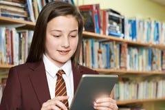 Uniforme scolastico d'uso della ragazza facendo uso della compressa di Digital in biblioteca Immagine Stock