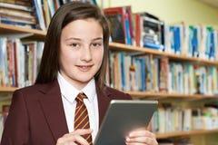 Uniforme scolastico d'uso della ragazza facendo uso della compressa di Digital in biblioteca Fotografia Stock Libera da Diritti