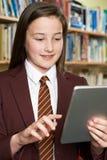 Uniforme scolastico d'uso della ragazza facendo uso della compressa di Digital in biblioteca Fotografia Stock