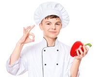 Uniforme vestindo do cozinheiro chefe do menino adolescente Foto de Stock